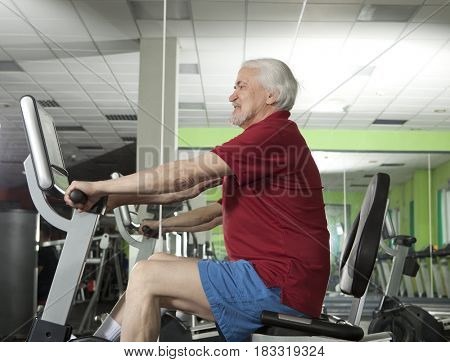 Senior man spinning on fitness bike in fitness center