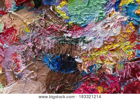 Palette with colorful mixed oil-paints texture on canvas, close-up, modern art, object