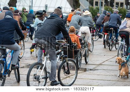RIGA LATVIA - APRIL 22 2017: Tweed ride 2017. A lot of unknown people in ancient costumes with bicycles traveling on city streets.