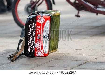 RIGA LATVIA - APRIL 22 2017: Tweed ride 2017. On the street next to a bicycle lying colorful accordion.