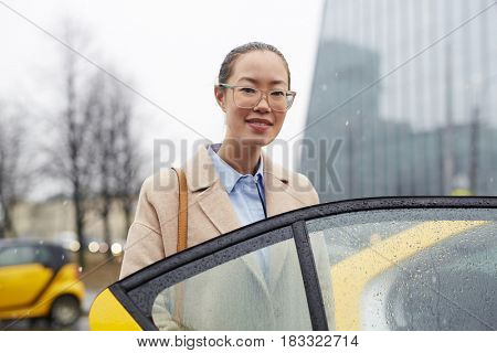 Pretty businesswoman looking at camera by open taxi door