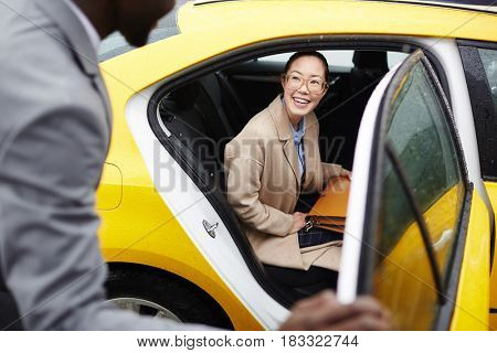 Young woman sitting on backseat of taxi and talking to her business partner