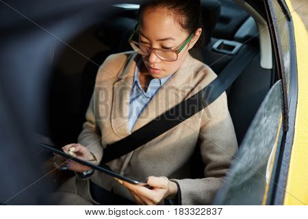 Mobile businesswoman with touchpad working online in taxi cab