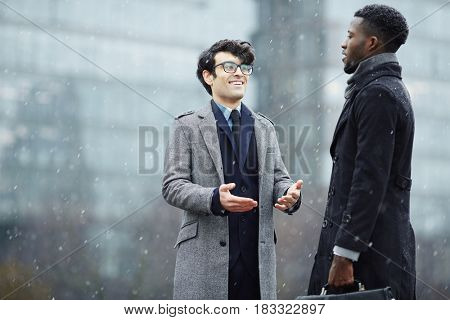 Intercultural businessmen having conversation on snowy weather