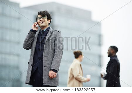 Businessman with mobile telephone calling on background of two co-workers