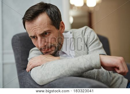 Stressed man sitting in armchair and crying
