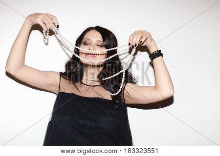 Cheerful woman putting on the diadem. Horizontal studio shot.