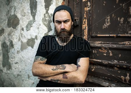 Portrait of brutal bearded man wearing blank t-shirt on the door. Men with tattoo looking at the camera. Folded his arms over his chest