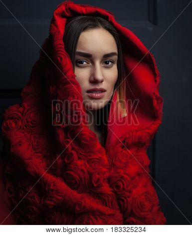 beautiful woman red cloak with red flowers roses in studio. Woman Red Riding Hood. Dramatic and fantastic shooting fashionable toning. Like a princess