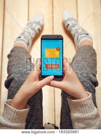 Girl with a phone in her hands sitting on the wooden floor. top view