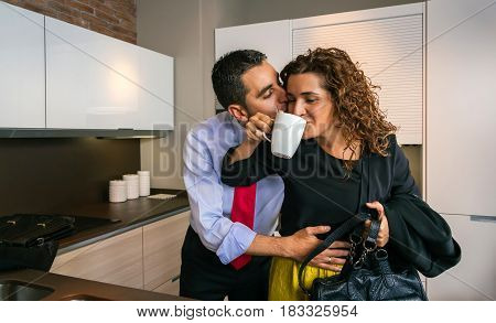 Young businessman embracing and kissing to happy curly woman while drinking fast cup of coffee before go to work