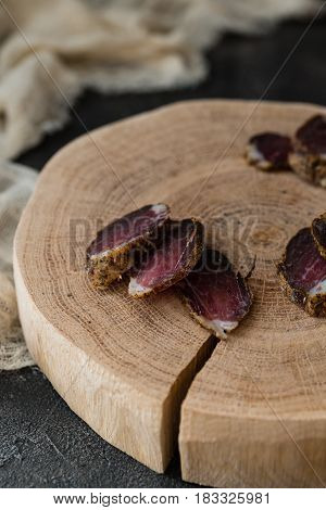 Slices Of Dried Meat On Wooden Cut On Dark Rustic Background. Snack And Appetizer Concept