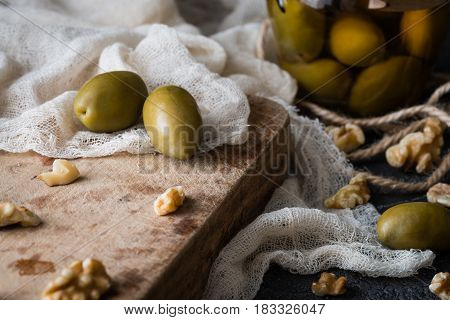 Green olives and walnuts on old wooden board on a dark rustic background. Accompanying snack or appetizer