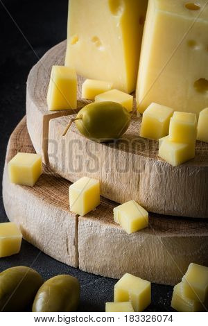 Close Up Of Swedish Hard Yellow Cheese With Holes Chopped On Wooden Slices With Green Olives On Dark