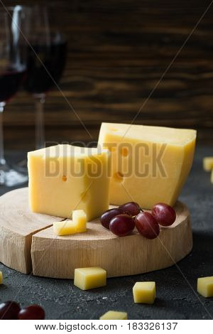 Swedish Hard Yellow Cheese With Holes Chopped With Red Grapes On Wooden Slices And Glasses With Red