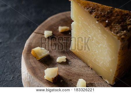 Italian Hard Cheese Pecorino Toscano Chopped On Wooden Cut On Dark Rustic Background