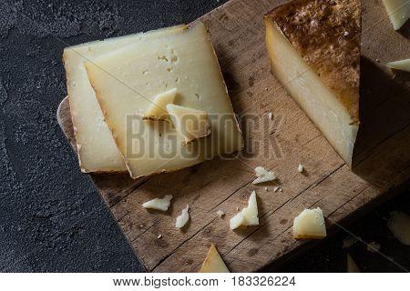 Italian Hard Cheese Pecorino Toscano Sliced And Chopped On Wooden Board On Dark Rustic Background