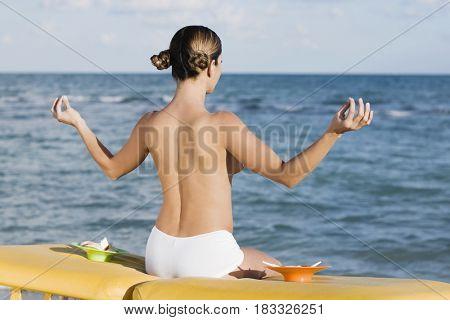 Topless Hispanic woman meditating