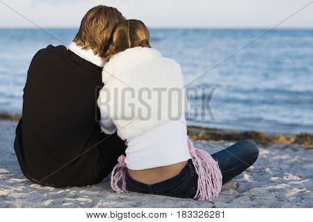 Hispanic couple sitting on beach