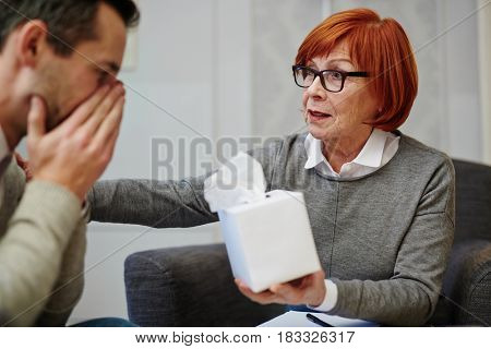 Helpful psychologist offering her client tissues to wipe tears
