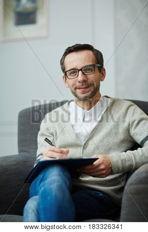 Succesful counselor making notes while listening to patient