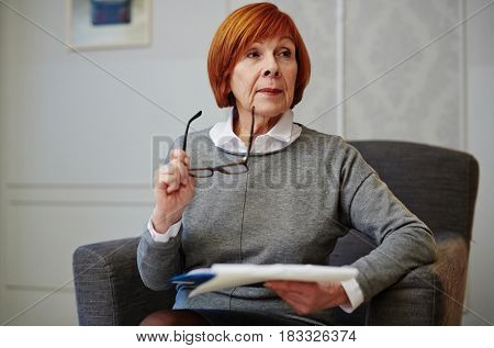 Concentrating mature woman sitting in armchair