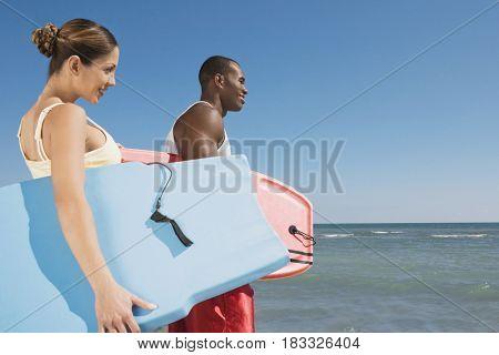 Multi-ethnic couple holding bodyboards