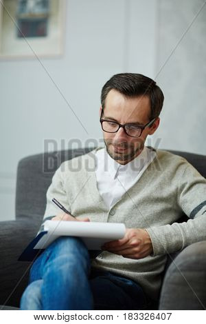 Serious psychologist making notes while listening to patient story