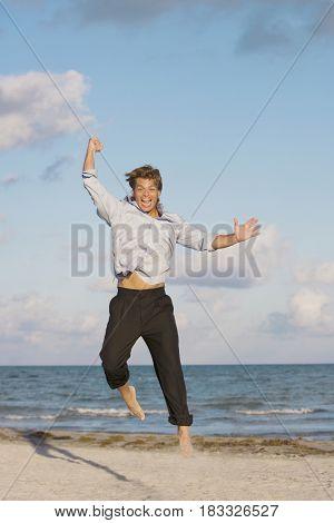 Hispanic man jumping on beach