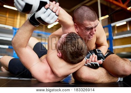 Portrait of shirtless professional wrestlers fighting in boxing ring: throwing opponent on floor and headlocking in submission hold
