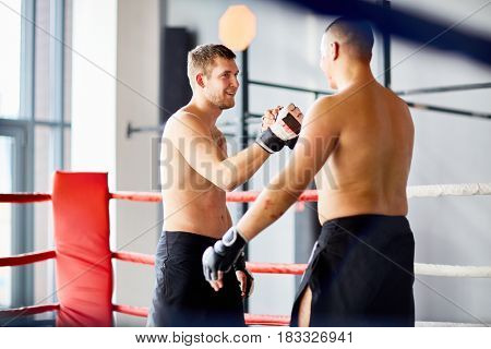 Portrait of two opponents shaking hands and smiling after good fight in boxing ring during practice