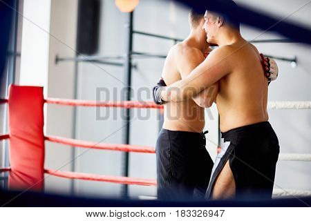 Portrait of two opponents hugging after good fight in boxing ring during practice
