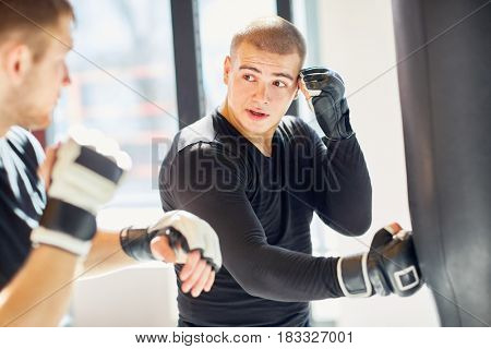 Portrait of young muscular sports man hitting punching bag during boxing practice in fight club, showing to his partner core speed hitting technique