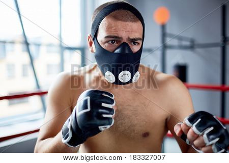 Portrait of shirtless boxer standing in  fighting pose in boxing ring wearing training mask