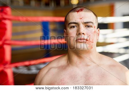 Portrait of strong muscular man looking at camera with determination after finishing fight in boxing ring, face covered in blood