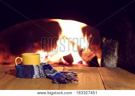 Yellow mug in a blue scarf on the background of a retro fireplace / warming pastime in the village