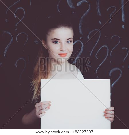 Young girl with question mark on a gray background.