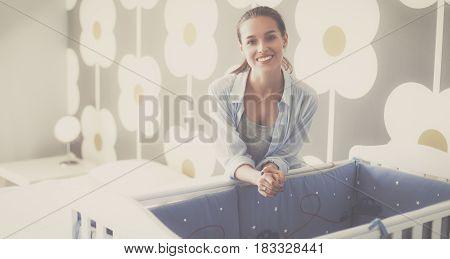 Young beautiful woman standing near children cot.