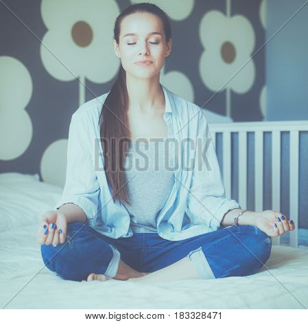 Young woman sitting on the bed near childrens cot.