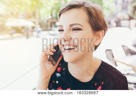 Close-up of a girl with short pixie haircut is having a phone conversation. People and technology concept.  Human face with expression emotions and feelings, laughing.