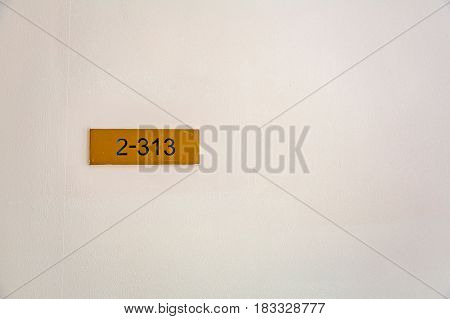 Yellow nameplate with black figures 2-313 hanging on a light wall