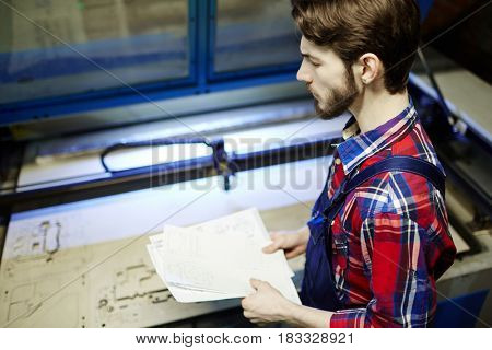 Worker of technical lab holding papers with sketches