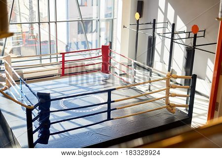High angle shot of empty boxing ring in sunlit fight club hall