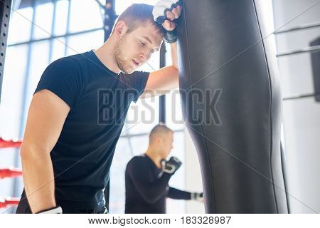 Low angle portrait of young tired sports man leaning on punching bag during boxing practice in fight club