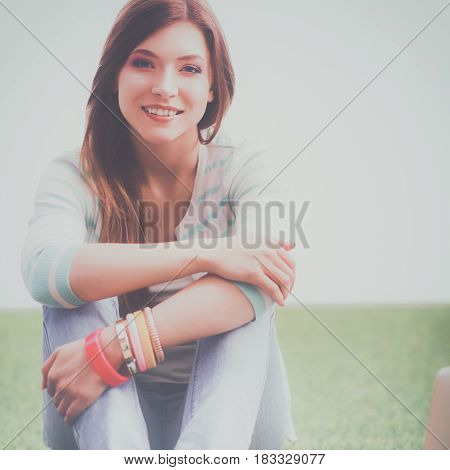 Beautiful young woman sitting on the green grass.