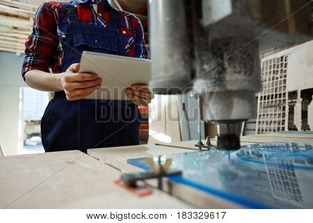 Mechanic in uniform looking for technical instructions in the net