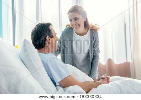 Side View Of Smiling Wife Visiting Elderly Husband In Hospital