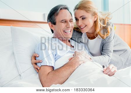 Portrait Of Happy Wife Visiting Elderly Husband In Hospital