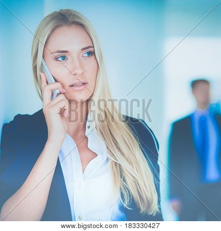 Businesswoman standing against office window talking on mobile phone.
