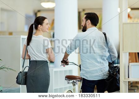 Back view portrait of casual Asian businessman taking bicycle to work and talking to colleague leaving modern creative office